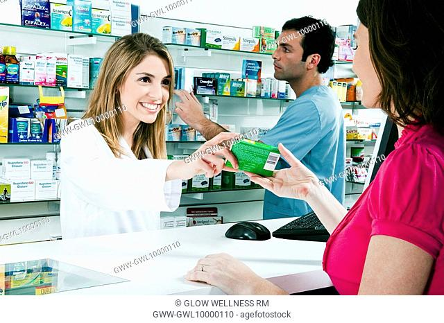 Female pharmacist giving medicine to a customer