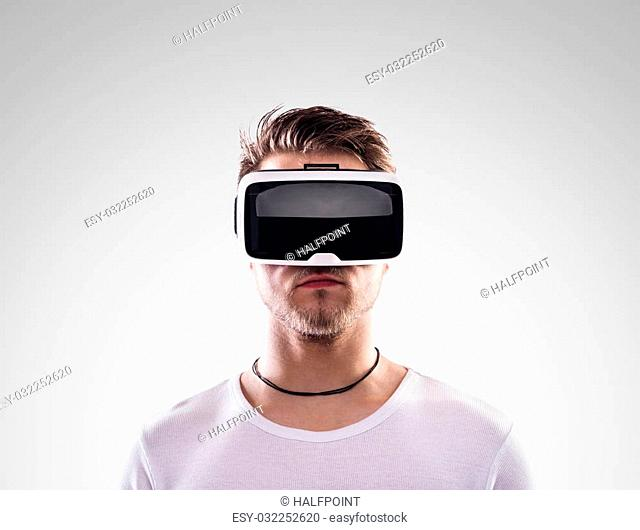 Hipster man in white t-shirt wearing virtual reality goggles. Studio shot on gray background