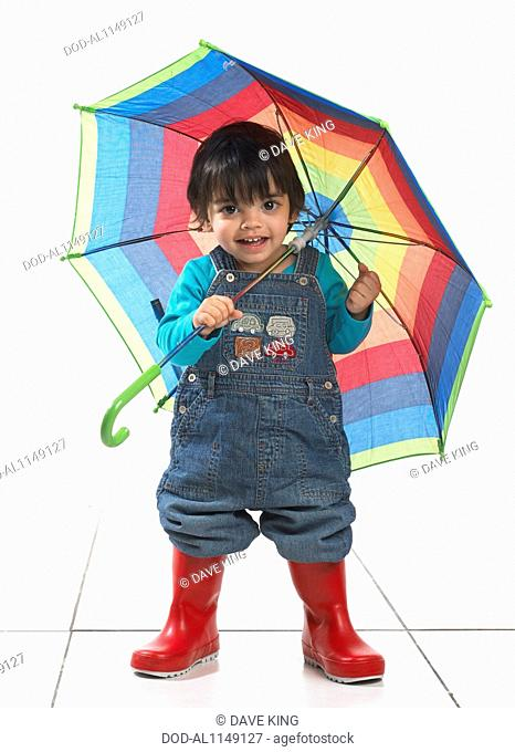 Small boy (16 months) wearing wellington boots and holding umbrella