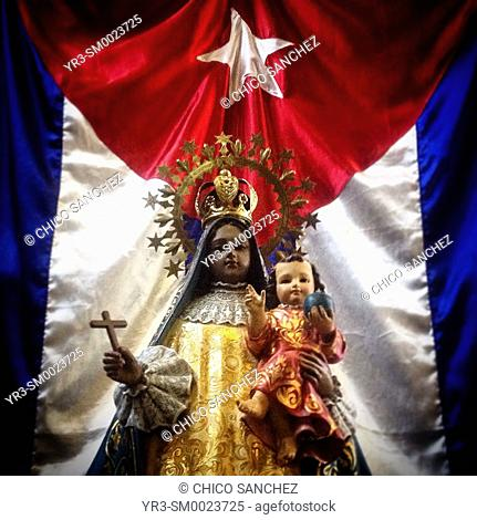 A Cuban flag displayed behind an image of Our Lady of Charity, known also like Our Lady of El Cobre, in a church in Polanco, Mexico