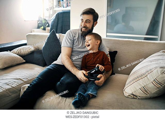 Happy father and son sitting together on the couch playing computer game