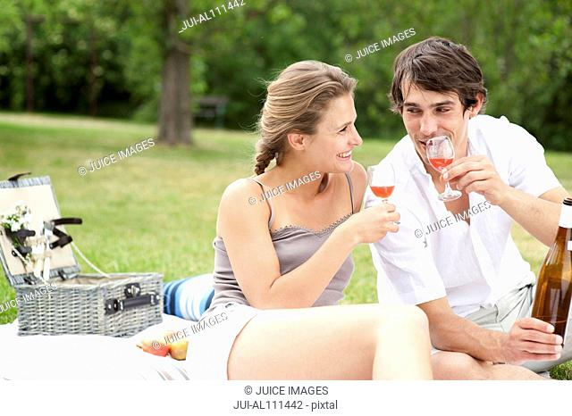 Young couple drinking wine at picnic in park