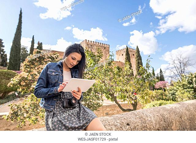 Spain, Granada, young woman using tablet at the Alhambra