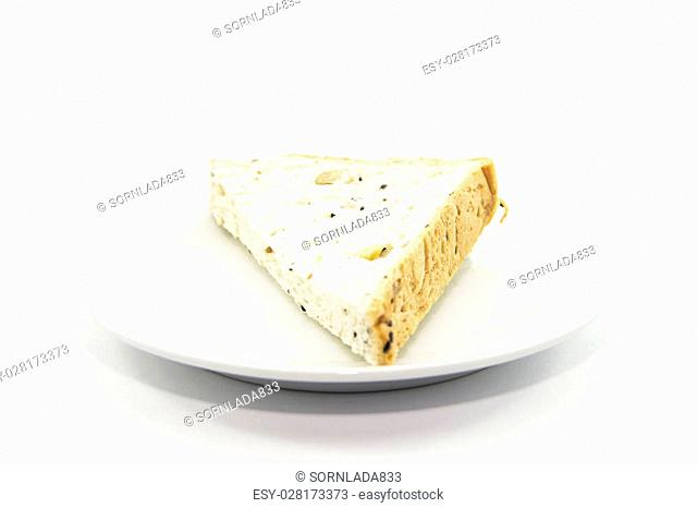 Whole grain bread section sliced on white plate on white background