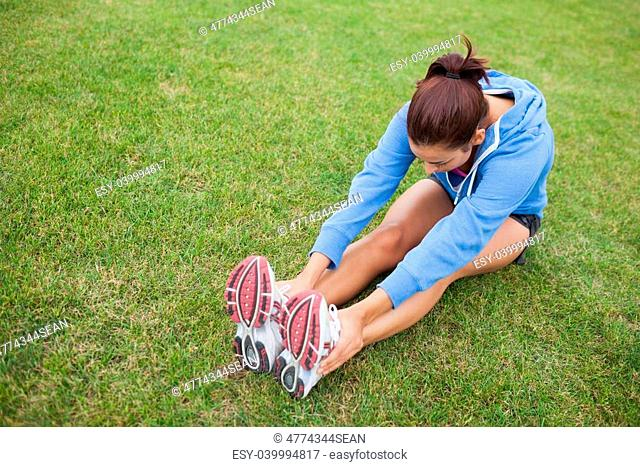 High angle view of a sporty woman stretching her legs while sitting on the grass