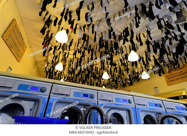 laundrette in the Äußere Neustadt, in the washing machin forgotten socks hanging from the ceiling, Germany, Saxony, Dresden