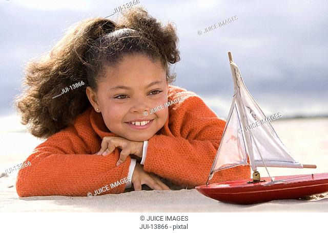 Girl 5-7 with toy boat on beach, smiling