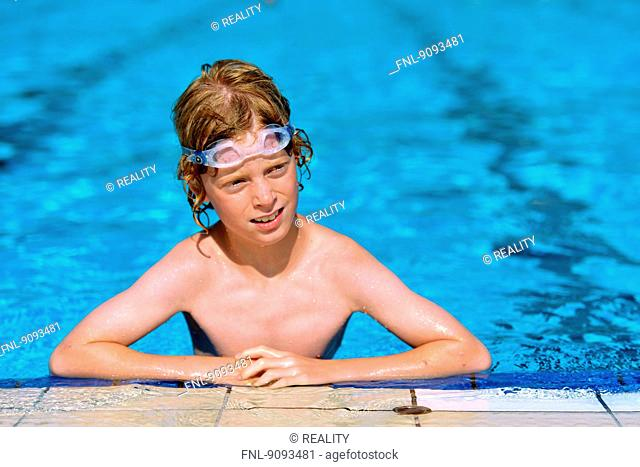 A boy with swimming goggles in an open air bath