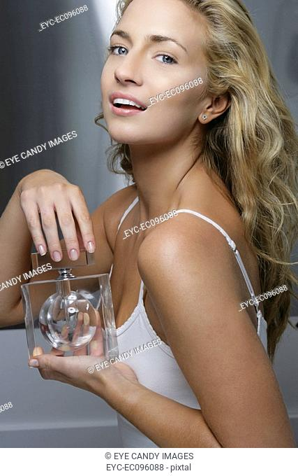 Profile of smiling woman holding a perfume bottle