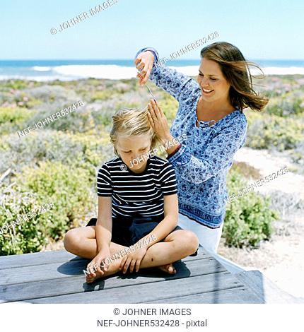 Scandinavian boy getting a haircut on the beach, Sweden