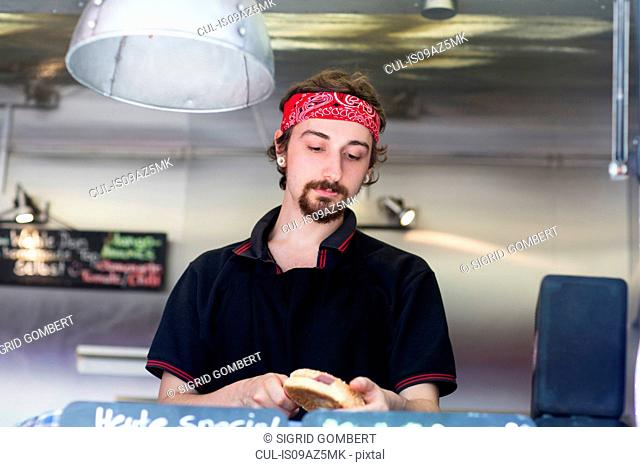 Young man slicing hamburger bread roll on fast food van