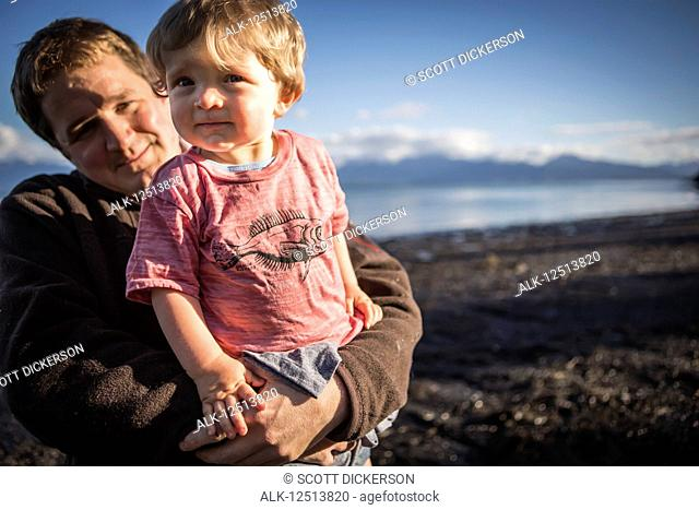 Father holds young toddler at sunset along the Homer beach, South-central Alaska; Homer, Alaska, United States of America