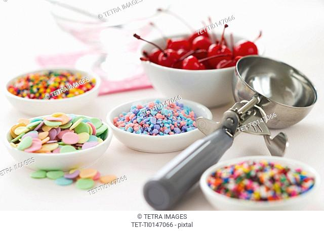 Close up of scoop and bowls with colorful toppings for ice creams