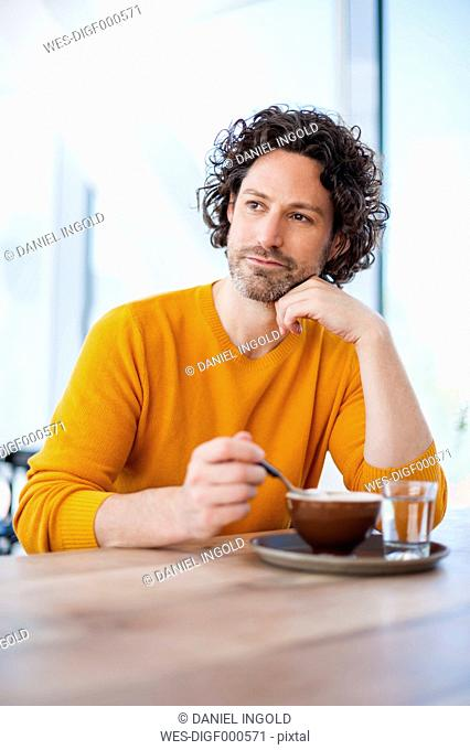 Portrait of pensive man with cup of Cappuccino