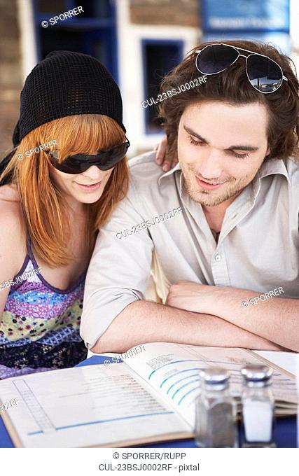 Young couple reading menu close up