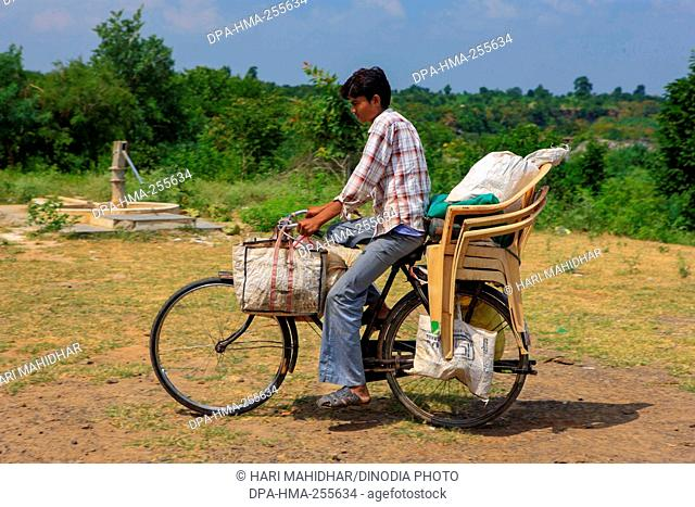 boy riding bicycle with household luggage, Madhya Pradesh, India, Asia