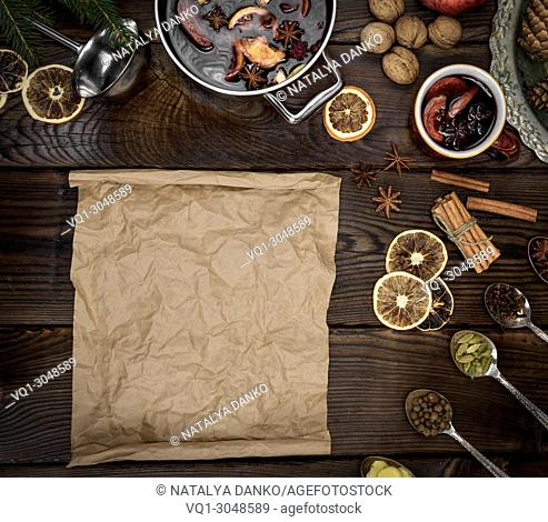 empty scroll of brown paper and ingredients for mulled wine preparation, top view