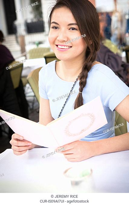 Young woman sitting at table at outdoor restaurant, holding menu