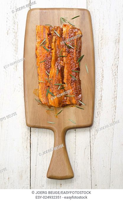 paprika marinated pork belly with rosemary on wooden board