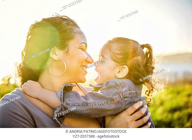 Mother and daughter embracing with the sun behind them