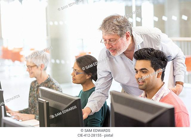 Professor helping student at computer in adult education classroom