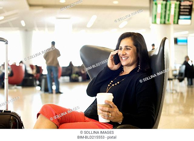 Hispanic businesswoman talking on cell phone in airport waiting area