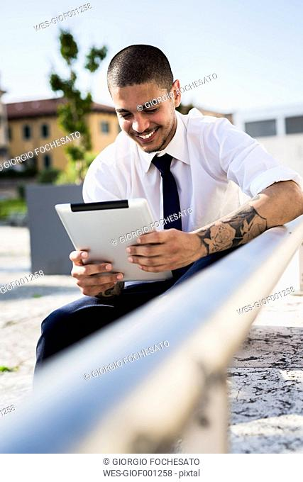 Smiling young businessman with tablet