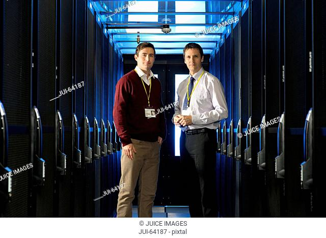 Manager and technician, looking at camera, in aisle of server room