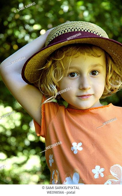 Little girl wearing a straw hat, Provence, France