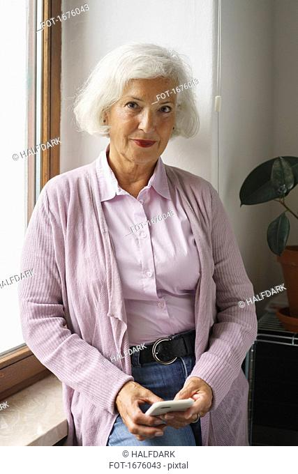 Portrait of senior woman with mobile phone leaning on window sill at office