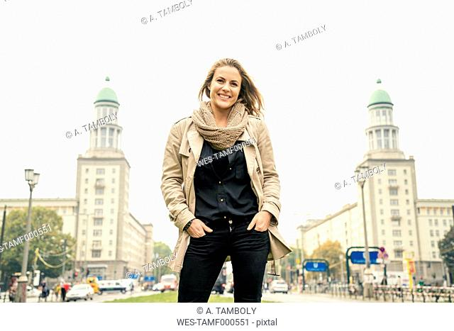 Germany, Berlin, portrait of smiling blond woman standing in front of Karl-Marx-Allee