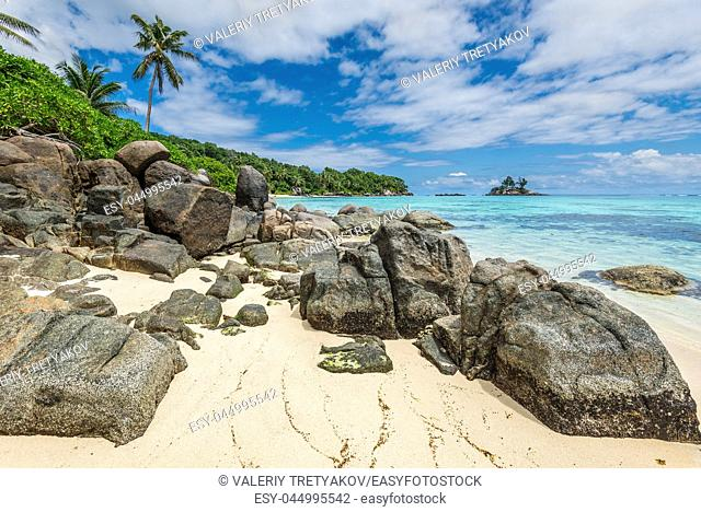 Seychelles seascape with granite boulders in the foreground - Ance Royale Beach in Mahe Island, Seychelles - is one of the favorite places for tourists because...
