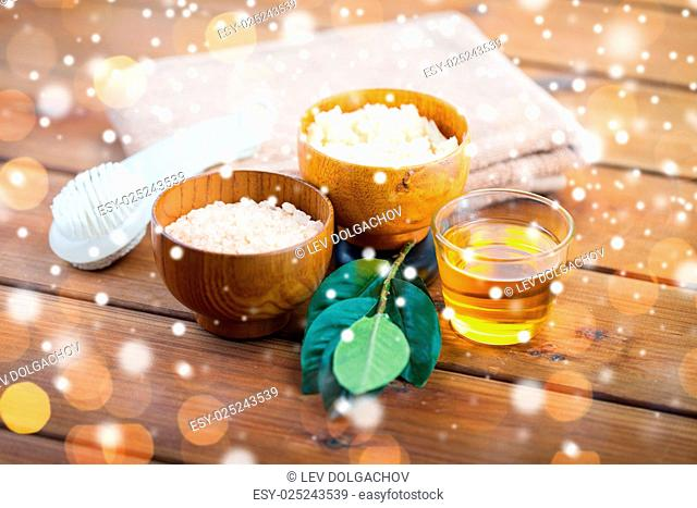 beauty, spa, bodycare, natural cosmetics and bath concept - close up of himalayan pink salt and body scrub with brush and towel on wooden table over lights and...