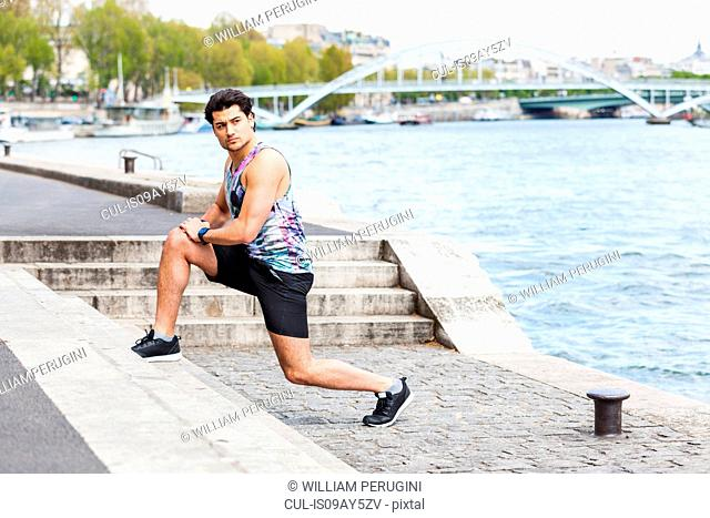 Young man exercising outdoors, stretching