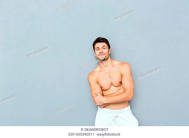 Smiling confident shirtless young man standing with arms crossed over grey background