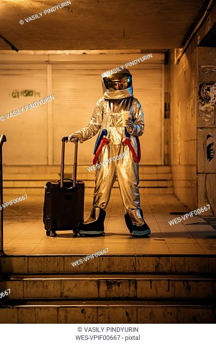 Spaceman in the city at night standing in underpass with rolling suitcase and takeaway coffee