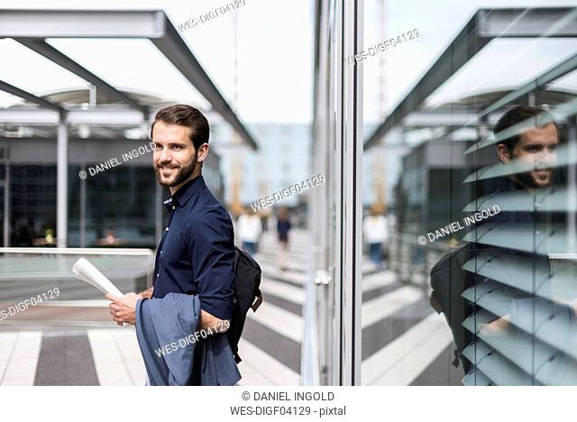 Smiling young businessman standing outdoors holding newspaper