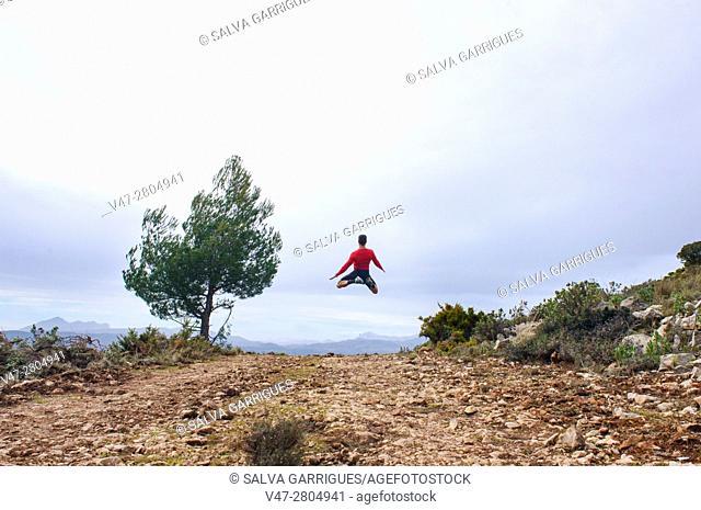 Sportsman jumping through the air in the mountains of Quatretondeta, Alicante, Valencia, Spain