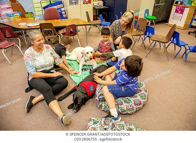 Multiracial young students hug a therapy dog on the floor of an elementary school classroom in Mission Viejo, CA. Note teacher and mother
