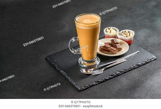 left side view on an aromatic coffee latte with two muffins and chocolate chips on a white saucer with a spoon and forks, the whole on a black stone plate