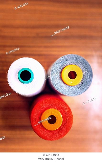 Directly above shot of multicolored thread spools on table at workshop