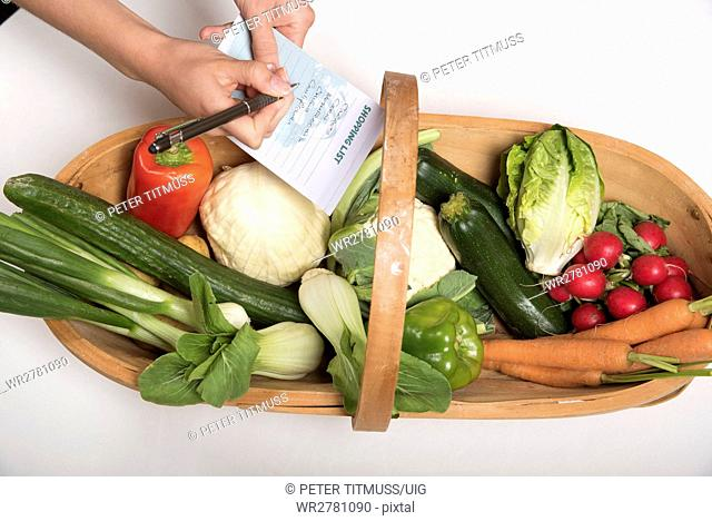 Garden trug with a selection of fresh produce Woman's hand holding shopping list