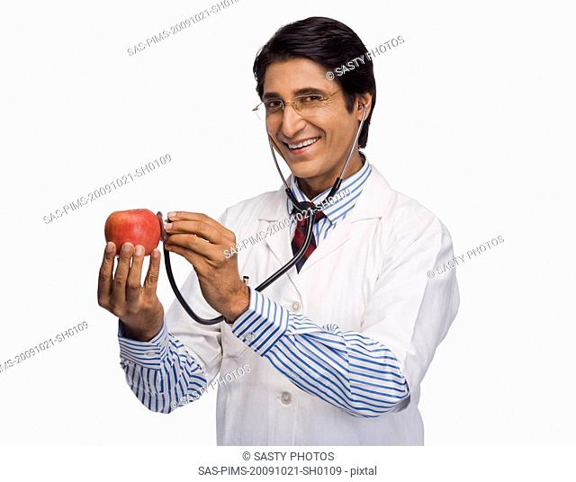 Portrait of a doctor listening to an apple with a stethoscope