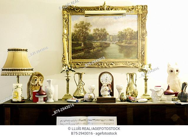 Piece of furniture with different objects: table light, clock, porcelain objects and a picture hung on the wall in a house. London, England