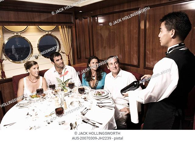 Waiter serving wine bottle to two mid adult couples