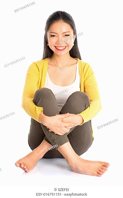 Full body Asian woman in yellow blouse seated on floor, isolated on white background