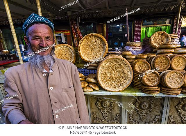 A Uyghur street vendor selling nang (flatbread) in the Bazaar, Kashgar is an oasis city in Xinjiang Province, China. It is the westernmost city in China