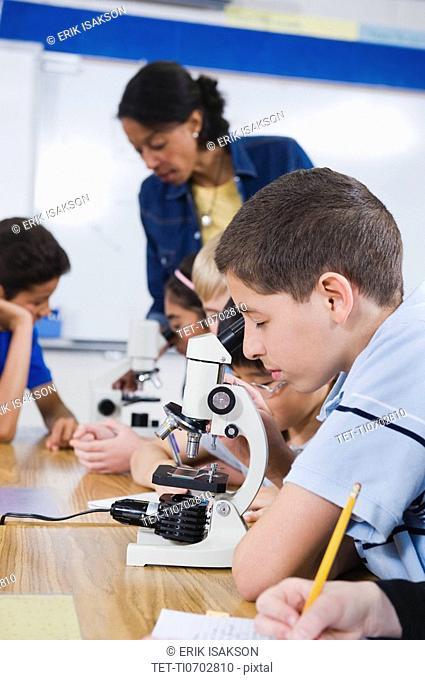 Elementary students using microscopes
