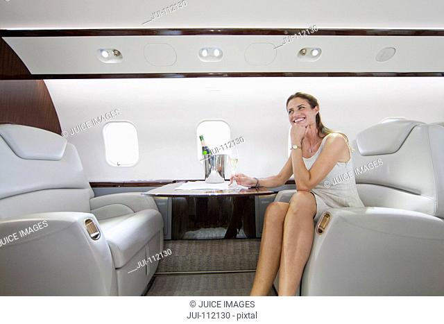 Attractive smiling woman sitting and holding champagne glass in private jet