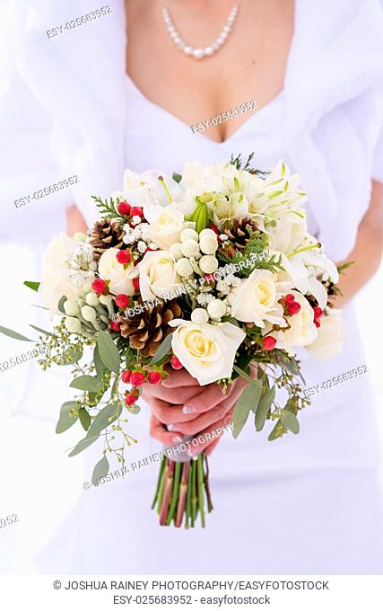 Bride holding a beautiful winter bouquet of flowers featuring white roses and holly berries in the snow